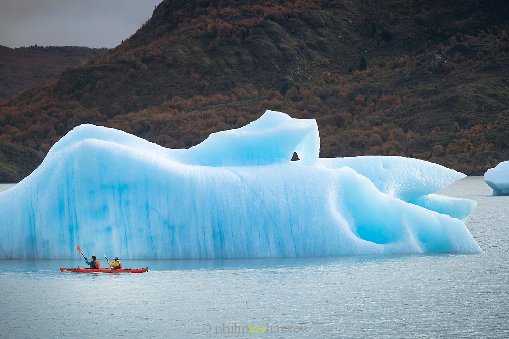 People kayaking by ice berg on Grey Lake in Torres del Paine National Park, Chile