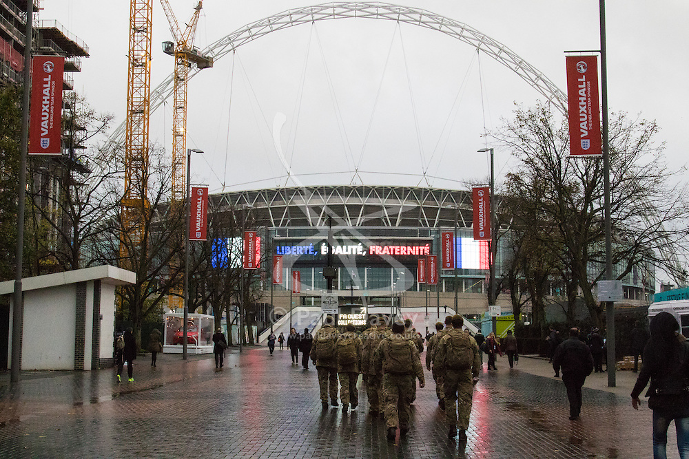 Wembley Stadium, London, November 17th 2015. Hours befor kick-off French and England fans begin to gather outside Wembley Stadium as both England and France national teams are poised to play in an emotional tie just days after the tragic death of 130 people in the Paris Islamist attacks. PICTURED:  Troops walk towards the stadium as security measures leave nothing to chance. // Licencing Contact: paul@pauldaveycreative.co.uk Mobile 07966 016 296