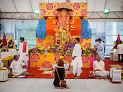 07 SEPTEMBER 2014 - BANGKOK, THAILAND: A woman prays in front of the main Ganesh statue while Hindu priests wait for people at the Ganesh Festival at Central World in Bangkok. Ganesh Chaturthi, also known as Vinayaka Chaturthi, is a Hindu festival dedicated to Lord Ganesh. It is a 10-day festival marking the birthday of Ganesh, who is widely worshiped for his auspicious beginnings. Ganesh is the patron of arts and sciences, the deity of intellect and wisdom -- identified by his elephant head. The holiday is celebrated for 10 days, in 2014, most Hindu temples will submerge their Ganesh shrines and deities on September 7.     PHOTO BY JACK KURTZ
