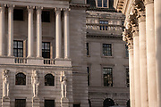 Mythical Greek male telamon figures look towards a female caryatid sculpture on the exterior of the Bank of England (left) and the columns of Royal Exchange (right) in the City of London, on 1st March 2021, in London, England.