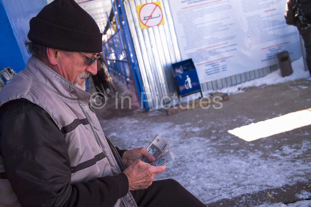 A skier counting his money at Beldersay ski resort on 27th February 2014 in Uzbekistan. Rather than buying a daily ski pass, you pay per chair lift. At the time the cost was 2000 som, about £2.20, for a ride to the top of the chairlift.