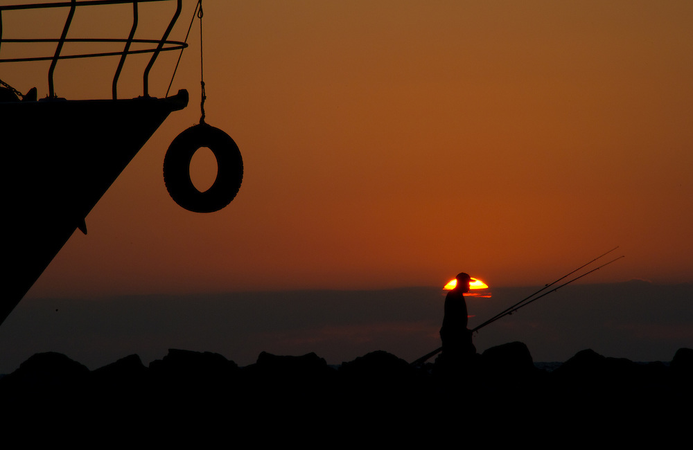 Fisherman against the sunset in Jaffa harbour