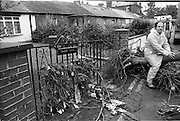 """Flooding at the Dodder..1986..26.08.1986..08.26.1986..28th August 1986..As a result of Hurricane Charly (Charlie) heavy overnight rainfall was the cause of severe flooding in the Donnybrook/Ballsbridge areas of Dublin. In a period of just 12 hours it was stated that 8 inches of rain had fallen. The Dodder,long regarded as a """"Flashy"""" river, burst its banks and caused great hardship to families in the 300 or so homes which were flooded. Council workers and the Fire Brigades did their best to try and alleviate some of the problems by removing debris and pumping out some of the homes affected..Note: """"Flashy"""" is a term given to a river which is prone to flooding as a result of heavy or sustained rainfall...Image of a workman taking a rest,sitting on an uprooted tree, at the point where the road subsided."""