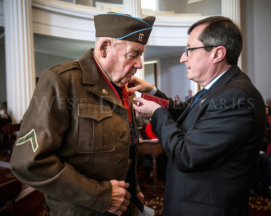 James M. Hamby of Valdese, N.C., private first class, Headquarters Battery, 29th Field Artillery Battalion, receives the Legion Of Honor award, France's highest recognition of French citizens or foreign nationals, from Denis Barbet, Counsel General of France, during a ceremony at the State Capitol honoring Hammy and six other veterans on Feb. 3 for their heroic acts saving countless French lives during World War II.