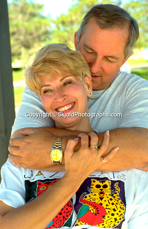Couple age 54 embracing on The Great River State Park Bike Trail.  Onalaska  Wisconsin USA