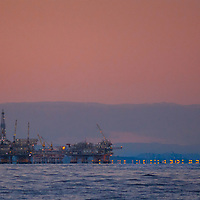 Oil drilling and pumping platforms rise out of the Pacific Ocean near Los Angeles, California. Behind is Long Beach Harbor.