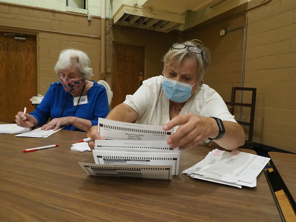 Poll worker Donna Nielsen checks that all fields are filled out properly on an absentee mail-in ballot as Nan Cycenas records the ballot is received. Absentee ballots are opened and counted on Election Day.