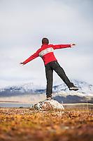 Female balances on rock in Autumn mountain landscape, Kungsleden trail, Lappland, Sweden
