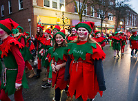 """""""Glitter"""" and """"Freckles"""" march with their fellow elves from Santa's Village during Light Up Laconia's Holiday Parade on Sunday.  (Karen Bobotas/for the Laconia Daily Sun)"""