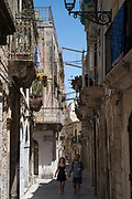 Street scene of young couple walking in ornate alleyway Via Dione in Ortigia, Syracuse, Sicily