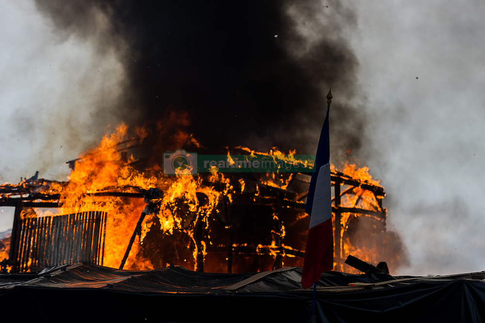 October 26, 2016 - Calais, France - A french flag hangs in the Calais Jungle in front of the flames of a burning hut, on October 26, 2016. Huge fires destroyed a mayor part of the refugee camp today. (Credit Image: © Markus Heine/NurPhoto via ZUMA Press)