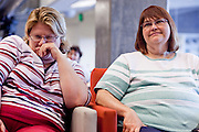 23 JULY 2009 -- PHOENIX, AZ:  Cindy Coffman (CQ) LEFT and Mary Cook (CQ), both staffers at the Cronkite School, chuckle while they listen to Sanford Socolow eulogize Walter Cronkite with some funny stories about the anchor's career. About 35 people gathered at ASU's Cronkite School Thursday to watch the live feed of the funeral of the school's namesake. Legenday CBS anchor Walter Cronkite died Friday, July 17.   PHOTO BY JACK KURTZ