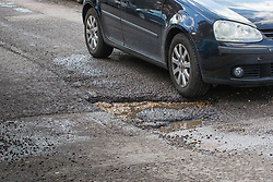 Risking a puncture or suspension damage a car passes through a deep pothole on Brondesbury Road in West London's Queens Park. The recent cold, wet weather has given rise to the increase in potholes and road surface deterioration in London. London, March 28 2018.