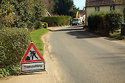 Tree cutting red triangular road sign in village street, Shottisham, Suffolk, England