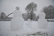 Snow man family in Kings Heath during heavy snow fall and build snow men on Sunday 10th December 2017 in Birmingham, United Kingdom. Deep snow arrived in much of the UK, closing roads and making driving treacherous, while many people simply enjoyed the weather.