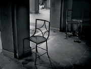 A chair sits in a dark room near an archway, illuminated by light coming in from outside