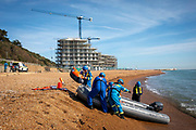 The Coast Guard drag a dinghy that brought 13 Asylum seekers safely to the beach on the 8th of October 2021 in Folkestone, United Kingdom. The Coast Guard support the Home Office to intercept and rescue small boats used by asylum seekers to cross the channel from France.