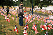 10 SEPTEMBER 2020 - DES MOINES, IOWA: A volunteer walks through a field of flags on the shore of Gray's Lake. About 25 volunteers braved cold and rainy weather Thursday to line the west end of Gray's Lake in Des Moines with American flags. The display of flags was a part of an annual event called the 9/11 Tribute Trail. About 3,000 flags were set out in memorial of the 3,000 people killed in the 9/11 terrorist attacks.     PHOTO BY JACK KURTZ