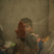 A child is seen sitting in a bed surrounded by a mosquito net at a bomb shelter in Donetsk's Petrovskiy District. Some of the around hundred residents moved to the old shelter almost four months ago, as when of the beginning of a major offensive against the city by the Ukrainian National Guard. Many of the city's residential areas have been increasingly destructed by regular shelling from both the Ukrainian troops and rebel forces.