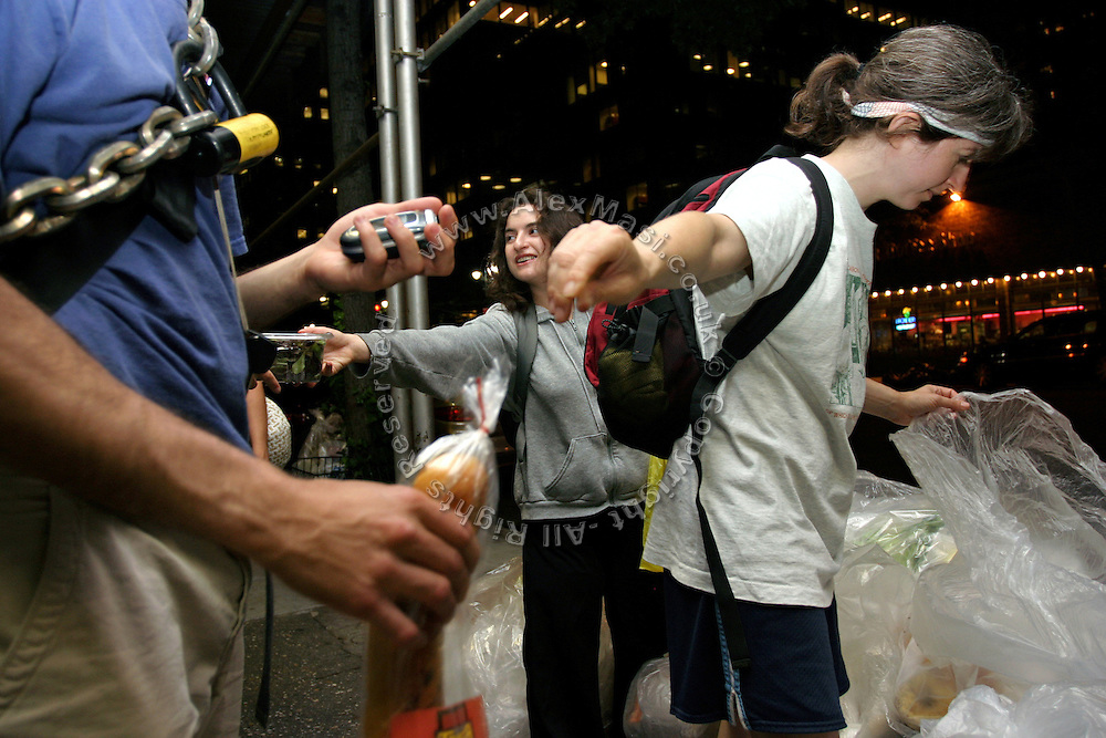 Janet, 43, one of the founders of the Freegan community in New York, and other Freegans recovering edible food from the rubbish during a trash tour along groceries on 3rd Avenue in Manhattan, New York, NY., on Wednesday, July 5, 2006. Freegans are a community of people who aims at recovering wasted food, books, clothing, office supplies and other items from the refuse of retail stores, frequently discarded in brand new condition. They recover goods not for profit, but to serve their own immediate needs and to share freely with others. According to a study by a USDA-commissioned study by Dr. Timothy Jones at the University of Arizona, half of all food in the United States is wasted at a cost of $100 billion dollars every year. Yet 4.4 million people in the United States alone are classified by the USDA as hungry. Global estimates place the annual rate of starvation deaths at well over 8 million. The massive waste generated in the process fills landfills and consumes land as new landfills are built. This waste stream also pollutes the environment, damages public health as landfills chemicals leak into the ground, and incinerators spew heavy metals back into the atmosphere. Freegans practice strategies for everyday living based on sharing resources, minimizing the detrimental impact of our consumption, and reducing and recovering waste and independence from the profit-driven economy. They are dismayed by the social and ecological costs of an economic model where only profit is valued, at the expense of the environment. In a society that worships competition and self-interest, Freegans advocate living ethical, free, and happy lives centred around community and the notion that a healthy society must function on interdependence. Freegans also believe that people have a right and responsibility to take back control of their time.