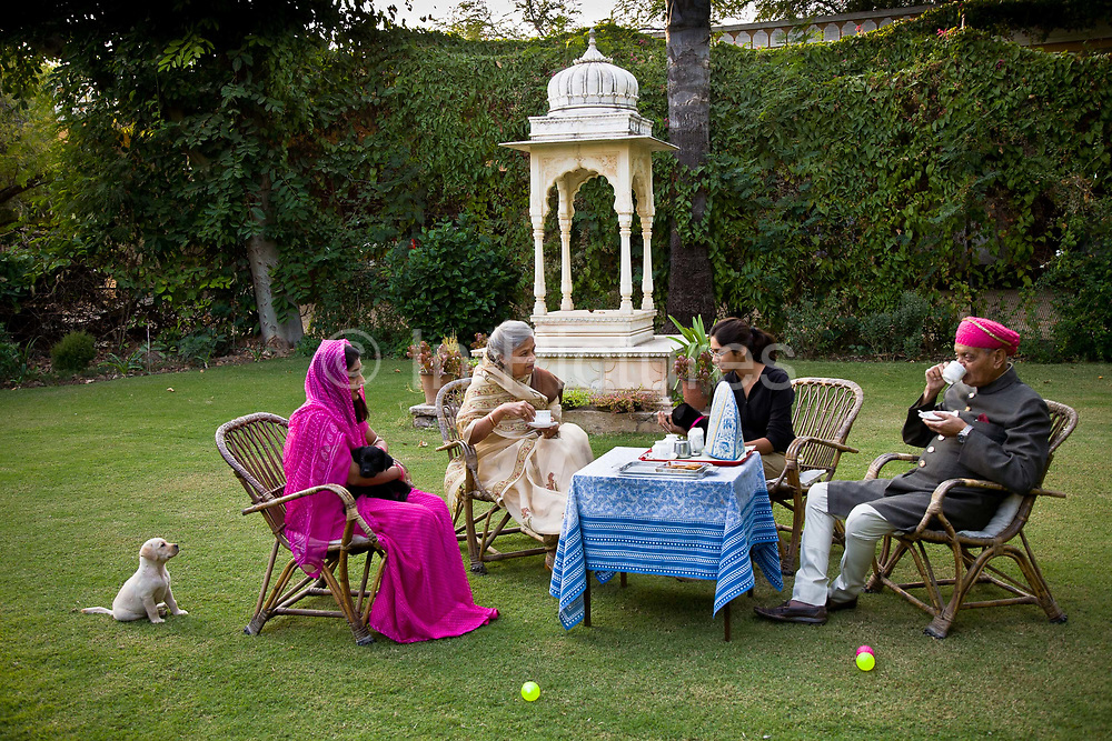 "Nobleman Nahar Singhji, also known as Rao Saheb, with his wife Rani Saheb, daughter-in-law and grandaughter, enjoy a genteel and relaxed cup of tea on the law of their lake side home on the grounds of the Deogarh Mahal Palace, now a heritage hotel.  This architectural jewel was, prior to it becoming so in 1996, a fortress - palace, dating back 340 years. It belonged to the Mewar aristocracy, their magnificent fort a fitting stronghold for one of its sixteen ""umraos"" - the most senior feudal barons attending on the Maharana of Udaipur, Rajasthan,"