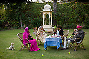 """Nobleman Nahar Singhji, also known as Rao Saheb, with his wife Rani Saheb, daughter-in-law and grandaughter, enjoy a genteel and relaxed cup of tea on the law of their lake side home on the grounds of the Deogarh Mahal Palace, now a heritage hotel.  This architectural jewel was, prior to it becoming so in 1996, a fortress - palace, dating back 340 years. It belonged to the Mewar aristocracy, their magnificent fort a fitting stronghold for one of its sixteen """"umraos"""" - the most senior feudal barons attending on the Maharana of Udaipur, Rajasthan,"""