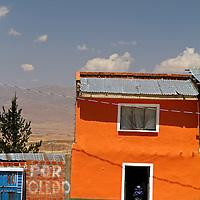 South America, Bolivia, Calamarca. Boy stands in the door of a Calamarca home.