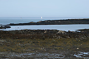 View out towards a sailing boat on the horizon and sea on 15th September 2020 in Cemlyn, Anglesey, Wales, United Kingdom. Cemlyn is a bay on the northwest coast of Anglesey, North Wales, within the community of Cylch-y-Garn. Separated from the bay by a shingle beach is a brackish lagoon, which is fed by a number of small streams.