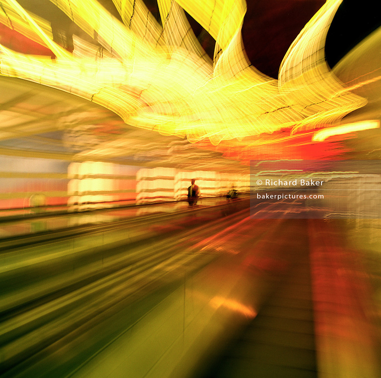 Blurred travellers on the escalator in an inter-terminal tunnel at Chicago-O'Hare airport, Illinois, USA. As the travelling escalator makes its way along the tunnel, colours and shapes blur except for a lone figure coming the other way, en-route to a departure or arrival gate in the public domain area of the airport hub, one of the largest airport in the United States, and 12 months before the terrorist attacks on America that changed the public's attitude to flying on commercial airliners.