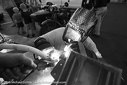 """Randy Aron  gets some help welding the cracked handlebars on his 1929 Harley-Davidson JD named """"Lucille"""" from another Cannonballer after the hosted dinner stop at Grand Junction Harley-Davidson during Stage 10 (278 miles) of the Motorcycle Cannonball Cross-Country Endurance Run, which on this day ran from Golden to Grand Junction, CO., USA. Tuesday, September 15, 2014.  Photography ©2014 Michael Lichter."""