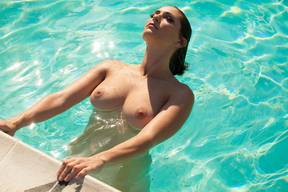 Nude woman leaning back and holding onto the edge of a swimming pool