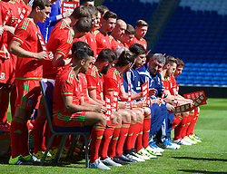 CARDIFF, WALES - Wednesday, June 3, 2015: Wales players hold up Show Racism The Red Card posters during a photo shoot at the Cardiff City Stadium ahead of the UEFA Euro 2016 Qualifying Round Group B match against Belgium. (Pic by Mark Hawkins/Propaganda)