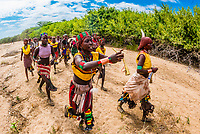 Women singing, dancing and jumping before the Hamer tribe bull jumping ceremony, a rite of passage initiating a boy into manhood, Omo Valley, Ethiopia.