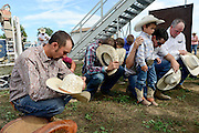 Bareback, bull and saddle bronc riders pray before the start of the CPRA Rodeo, Sunday, Aug. 3, 2014, in the Jack Murphy Arena at the Boulder County Fairgrounds in Longmont. Go to timescall.com for more photos.<br /> (Matthew Jonas/Longmont Times-Call)