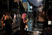 Young Muslim woman eats ice cream and passes-by a poster girl for Burberry sunglasses they call Eyewear, in London street. Burberry Group plc is a British luxury fashion house, manufacturing clothing, fragrance, and fashion accessories.