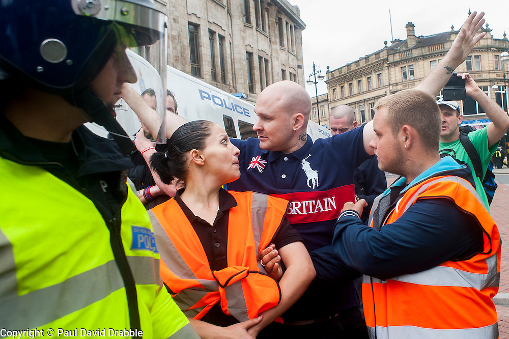 """Rotherham England<br /> 13 September 2014 <br /> EDL stewards and police marshal the English Defence Leagues """"Justice for the Rotherham 1400"""" March on Saturday Afternoon described by an EDL Facebook Page as """"a protest against the Pakistani Muslim grooming gangs"""" on Saturday Afternoon <br /> <br /> <br /> Image © Paul David Drabble <br /> www.pauldaviddrabble.co.uk"""
