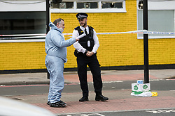 © Licensed to London News Pictures. 08/08/2017. LONDON, UK.  A police officer speaks to a forensic officer at the crime scene cordon on the corner of Old Kent Road and Ilderton Road, next to the Afrikiko Bar Restaurant and Club. Police were called at around 2am and found a 19 year old man with stab injuries, who was pronounced dead about an hour later. Five people have now been arrested in connection with stabbing and are being held at a south London police station.  Photo credit: Vickie Flores/LNP