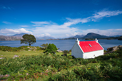 Small white cottage with red roof beside Loch Shieldaig in Torridon, on North Coast 500 tourist route, Highland, Scotland, United Kingdom.