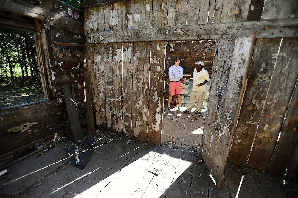 The disparity between 80-year-old Junior Meggett, right, and 21-year-old Burnet Rhett Maybank IV spans much more than generations. The Maybanks are part of lineage of families who owned the property known as Point of Pines Plantation since the 1674. The 18th-century slave cabin in which they stand was one of over two dozen cabins built by Maybank's descendent Charles Bailey in the 1840s or 1850s.  Meggett said he lived in a cabin on the property and his family worked on the plantation in the early 20th century. (Stephen Morton for The New York Times)