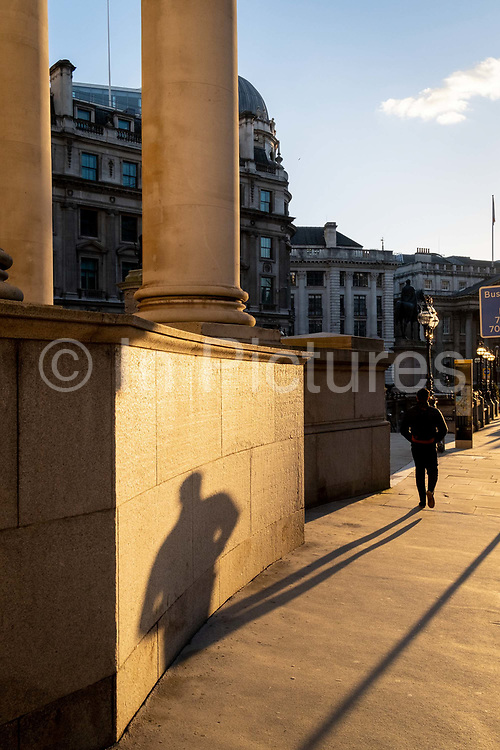 With most Londoners still working from home, a commuter leaves his shadow on a wall of Royal Exchange while walking along a quiet Threadneedle Street during the evening rush-hour during the third lockdown of the Coronavirus in the City of London, the capitals financial district, on 26th February 2021, in London, England.