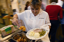 Ward Waitress serving out dinner onto a plate from food trolley,