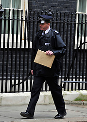 © Licensed to London News Pictures. 20/02/2012, London, UK. A police man delivers the protesters petition to number 10. Protesters outside Downing Street today. Protesters managed prevent Mr Landsley from entering the street for a short time. Andrew Landsley arrives in Downing Street for a meeting about the proposed reorganisation of the National Health Servie today 20 February 2012. Photo credit : Stephen Simpson/LNP