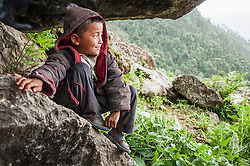 Boy sitting on rock and looking at mountain view, Nepal