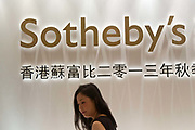 "A woman stands under a Southeby's sign outside of a Southeby's public preview of auction items in Shanghai, China September 04,  2013. Both Southeby's and Christie's have opened an office in Mainland China in the past year, however they face overwhelming odds as China's state-owned auction houses such as Poly and Jiamu enjoys a near monopoly over China's art procurement market as foreigners are not allowed to buy vaguely defined ""historical"" art."