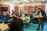 People sitting down to lunch at Slough Homeless our concern (SHOC) A local homeless charity helping the homeless and vulnerable in Slough. Berkshire, UK.