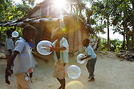 Children play with balloons made from condoms outside Merzelia Julien and Ynatus Etienne's small, two-room home on a mountain above Loncy village, Haiti. Funds from the nongovernmental organization ActionAid International help with various projects in the village, near Lascahobas, Haiti.