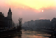 The seine river, bridge and buildings with the sun obscured by clouds and smog, 10th May 1980, Paris, France.