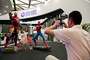 Two young visitors pose with models of Marvel comic heros Iron Man and Spider Man at the China Mobile booth of the ChinaJoy Expo, the annual online gaming expo, in Shanghai, China on 30 July, 2011.   China is now the world's largest online gaming market, contributing one-third to the global revenue in this sector in 2009, or 56 percent of the Asia Pacific total. Online and social network games have become hugely popular in China as Chinese children lack the space and facility require for sports, spurning worries from parents and government officials on internet addiction.