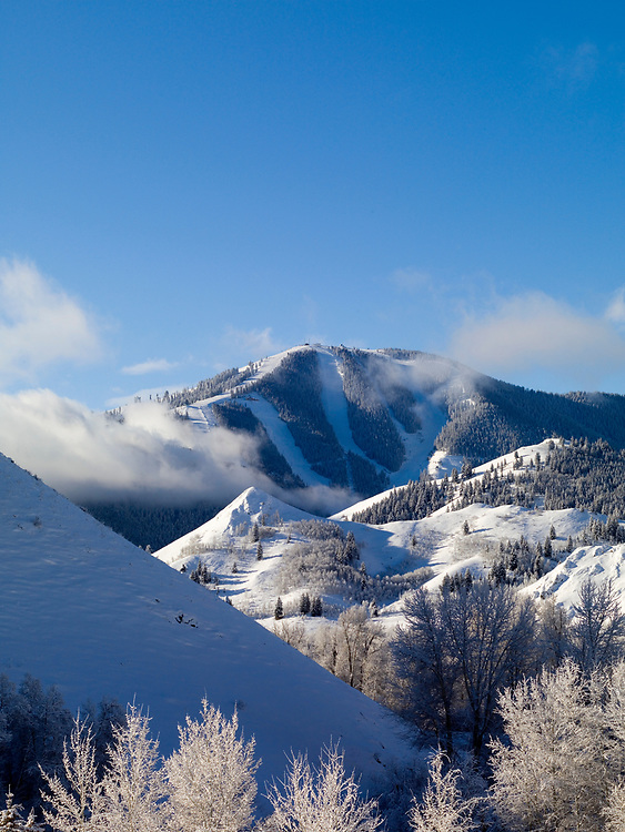 Fresh snow and lifting clouds shroud Sun Valleys Baldy Mountain on a winters morning from Lake Creek just north of Ketchum. Licensing and Open Edition Prints.