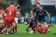 Eli Walker of the Ospreys (c) looks to break past the tackle from Morgan Allen of the Scarlets (on ground). Guinness Pro12 rugby match, Ospreys v Scarlets at the Liberty Stadium in Swansea, South Wales on Saturday 26th March 2016.<br /> pic by  Andrew Orchard, Andrew Orchard sports photography.